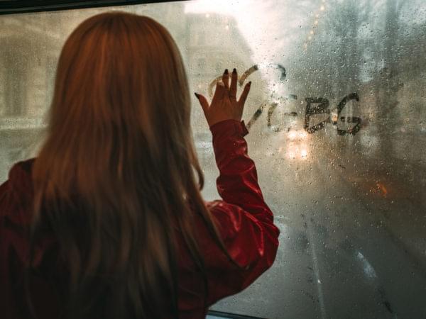 Kvinna som skriver i imman på fönstret.
