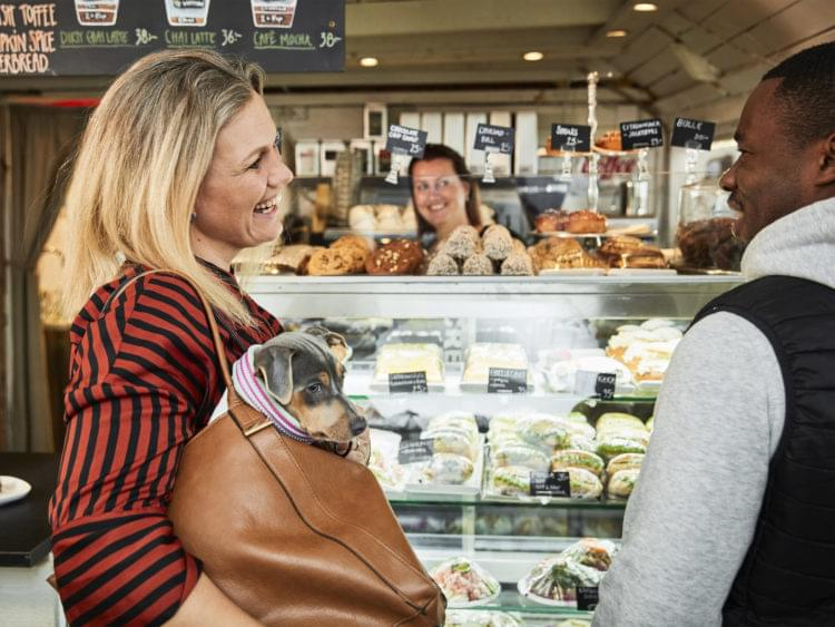 Två personer står framför en kafédisk. I kvinnans väska sitter en liten hund.