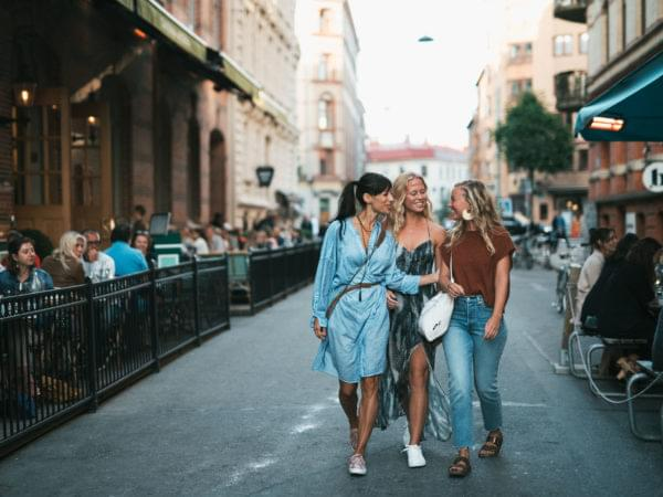 Tre kvinnor promenerar på Tredje Långgatan