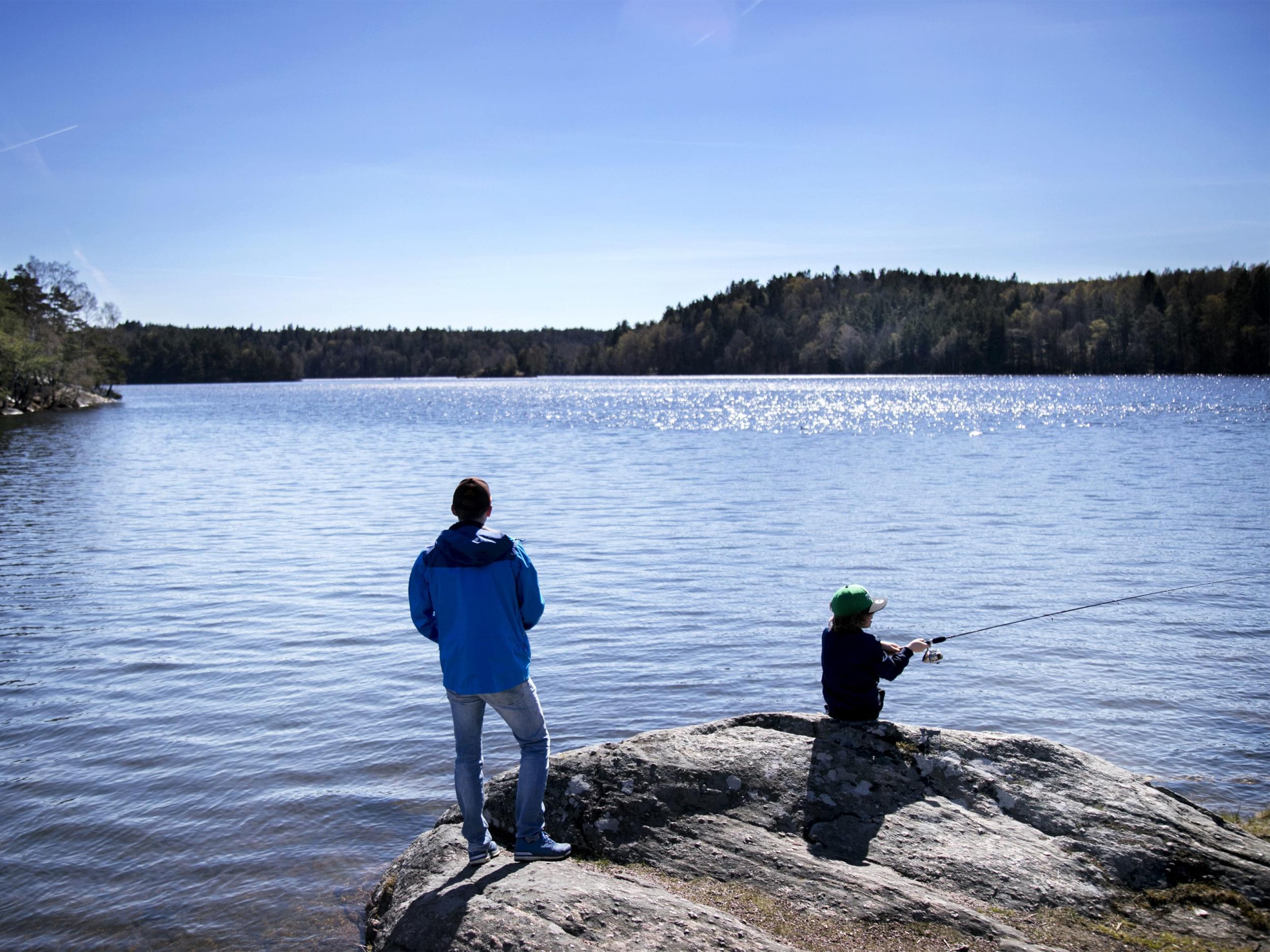 Vuxen och barn fiskar i en insjö.