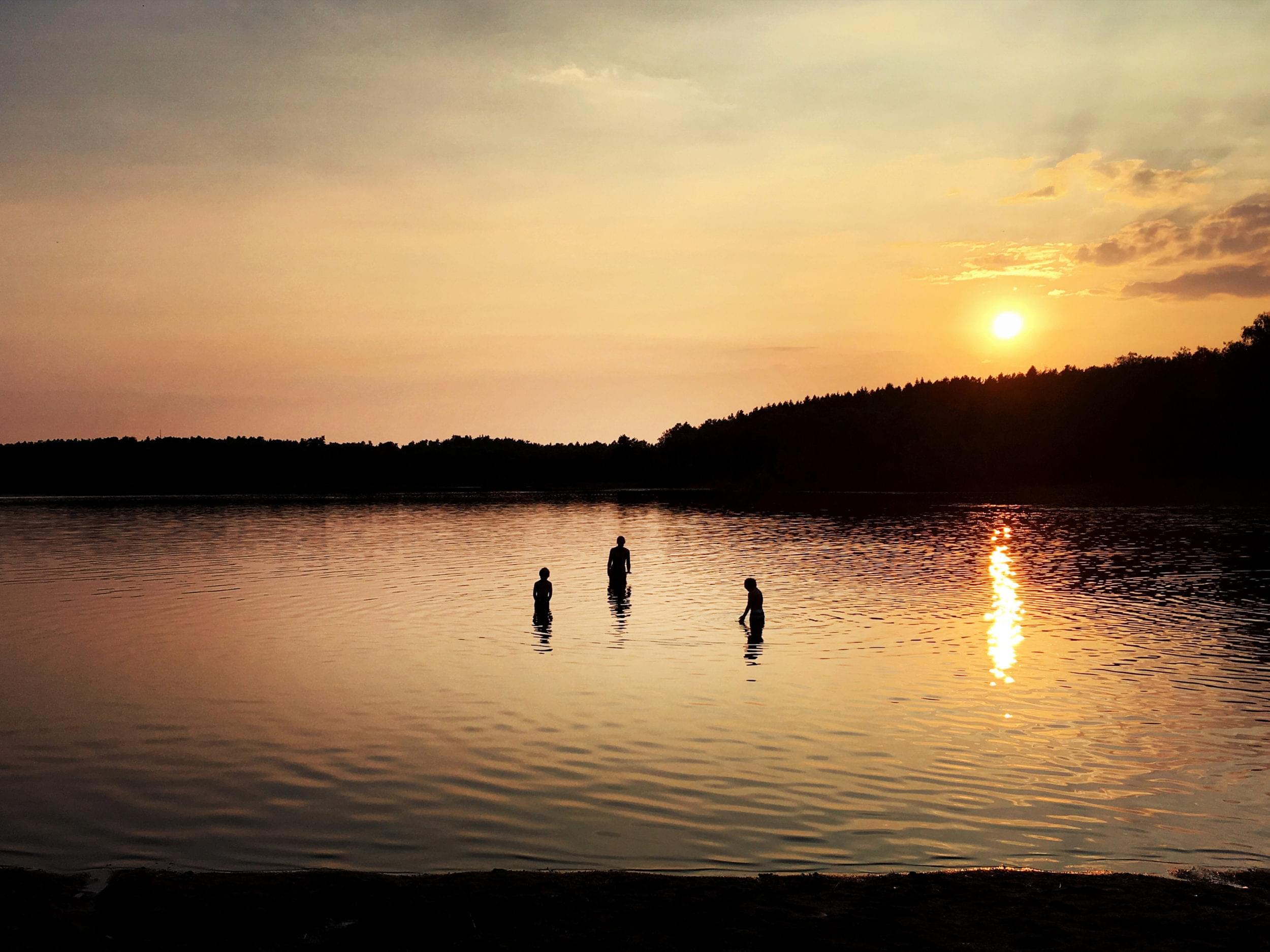 Tre personer bada i Härlanda Tjärn i kvällsljus.
