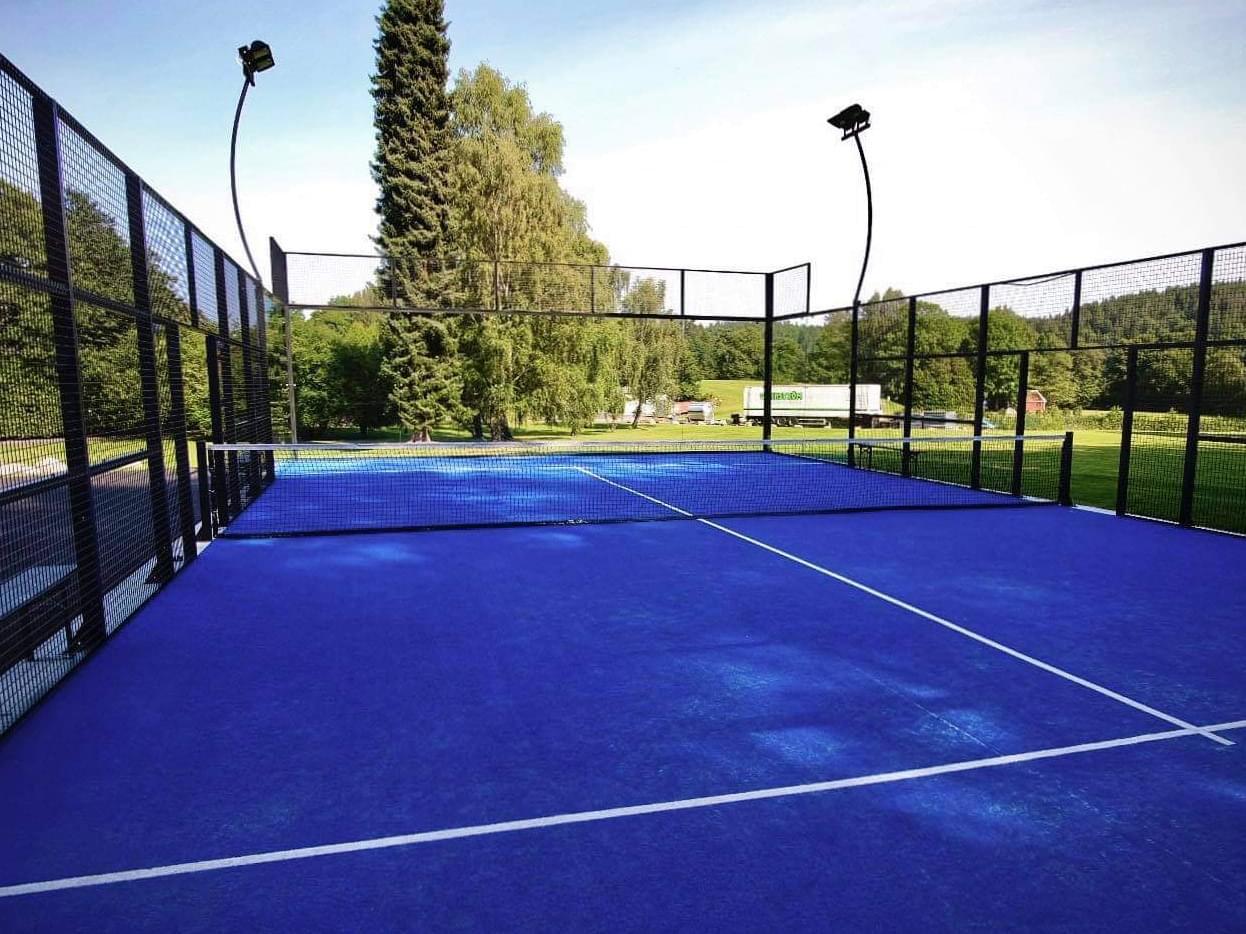 en padelbana med blå matta fotad från ena kortsidan