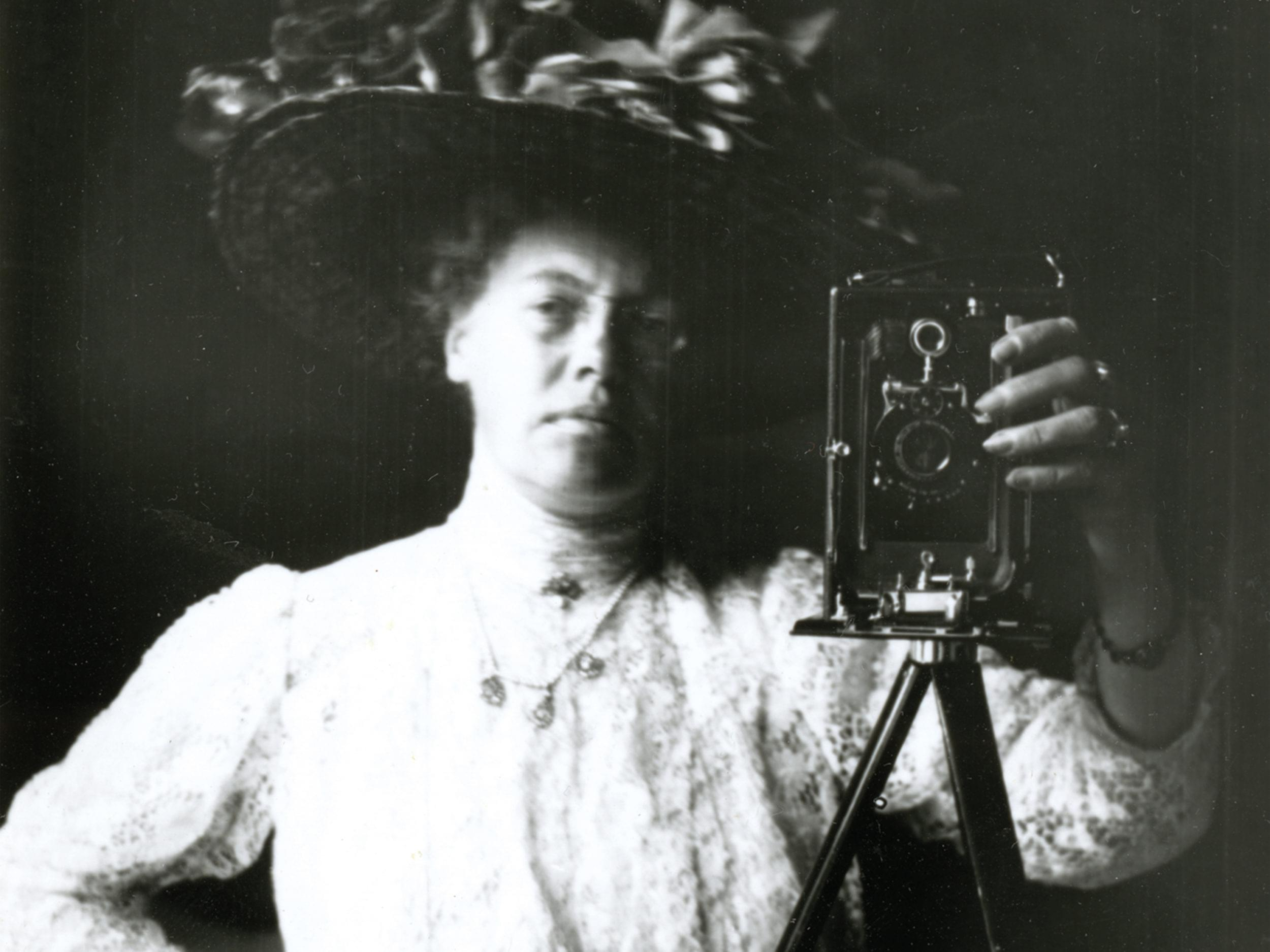 Ett svartvitt fotografi av en kvinna i stor hatt som fotograferar