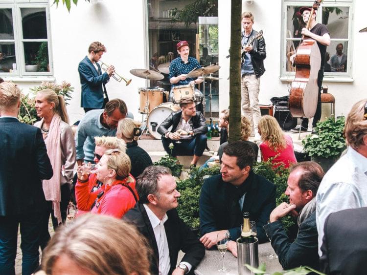 Folk minglar och dricker öl på innergård där ett jazzband spelar.