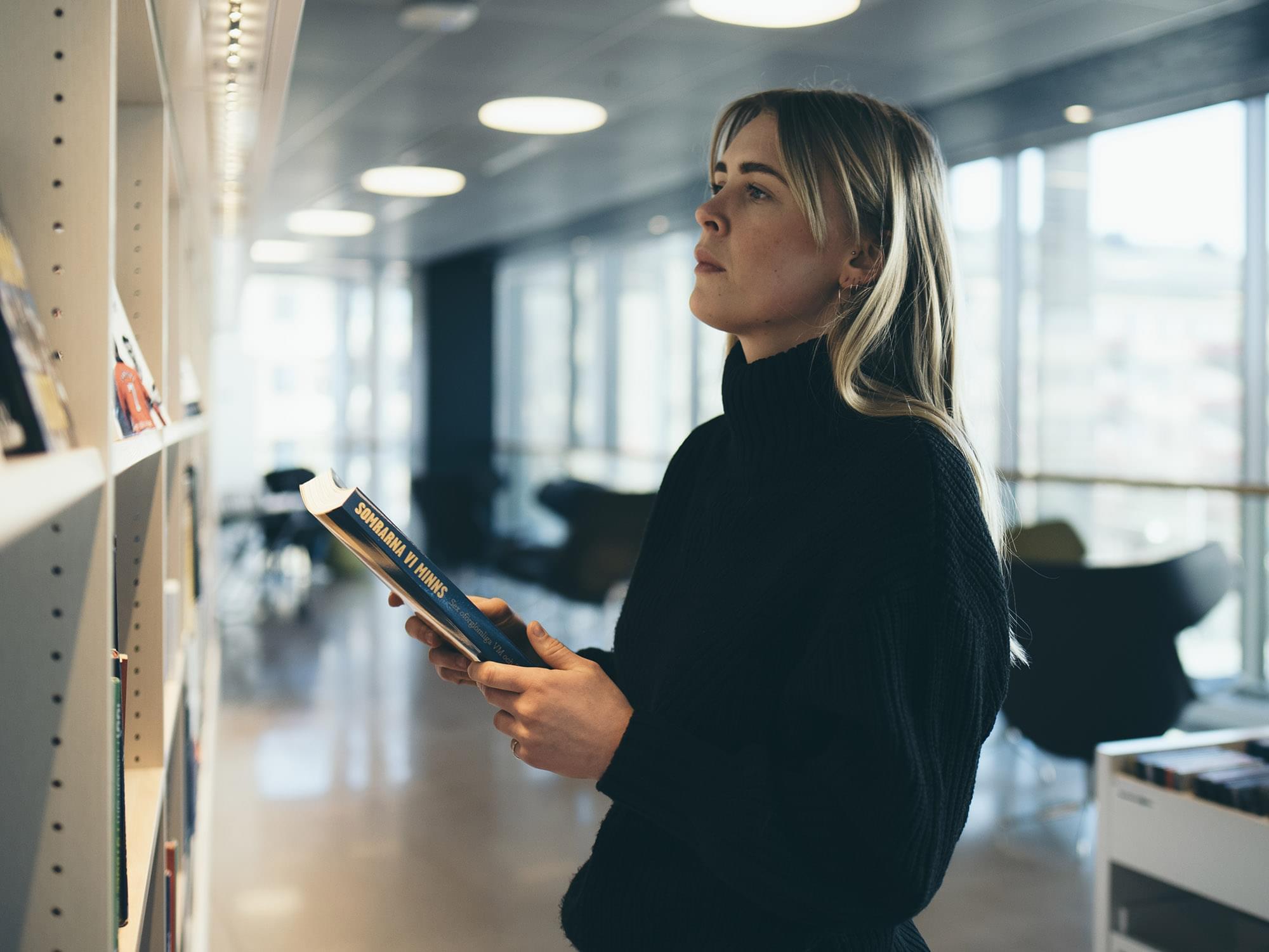 Kvinna står med bok vid bokhylla