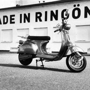 Svartvitt foto på en moped.