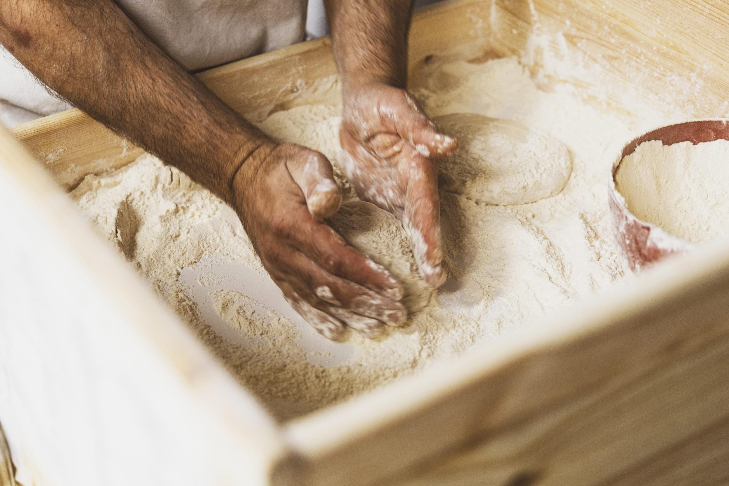 Två händer som knådar pizzadeg.