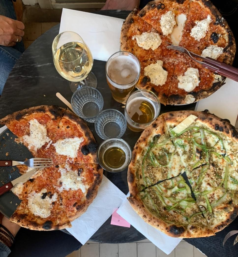 Tre pizzor och flera glas på ett bord, fotade ovanifrån.