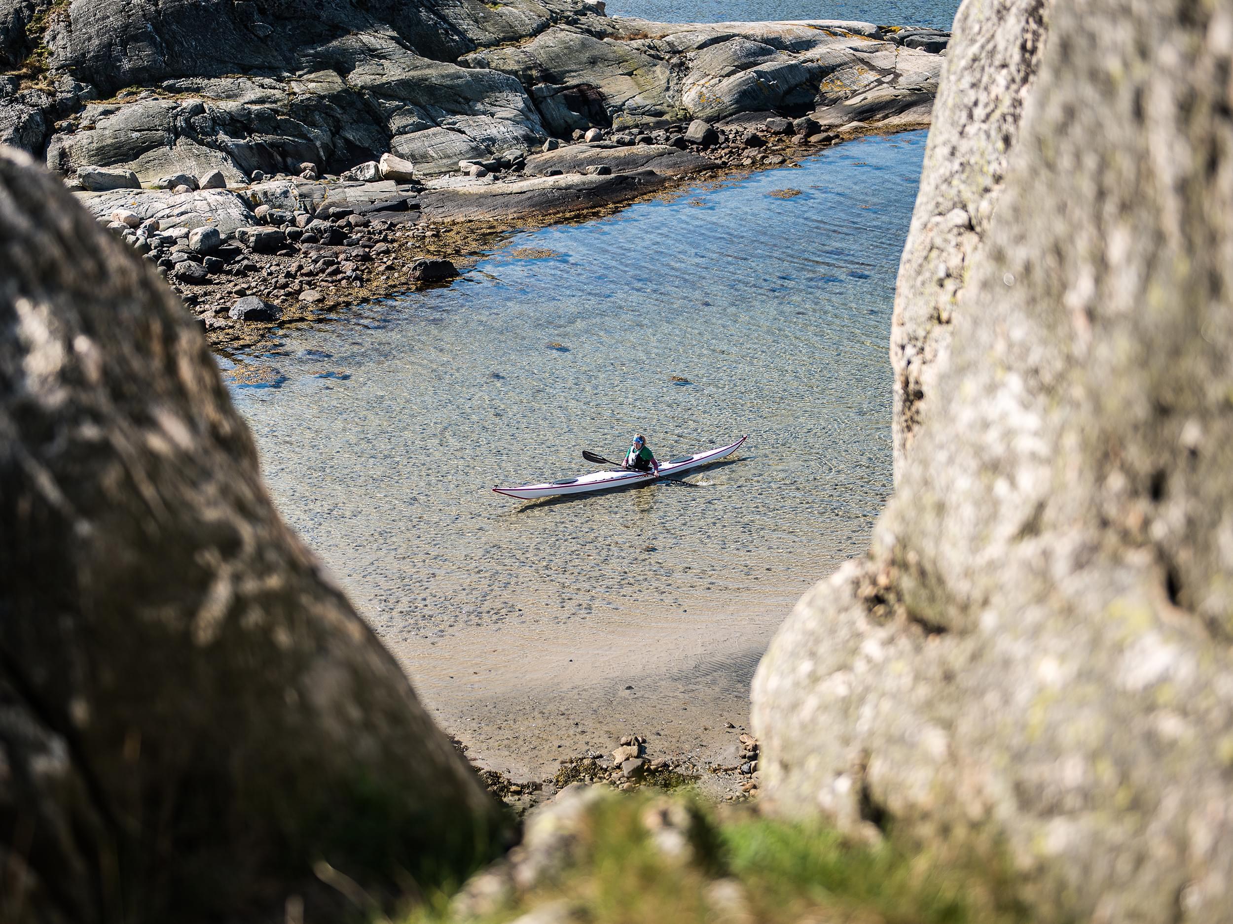 Kajak i en havsvik omgiven av klippor