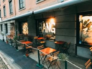 Utsidan av restaurang Bang. Stora fönster med texten BANG målade på dem.