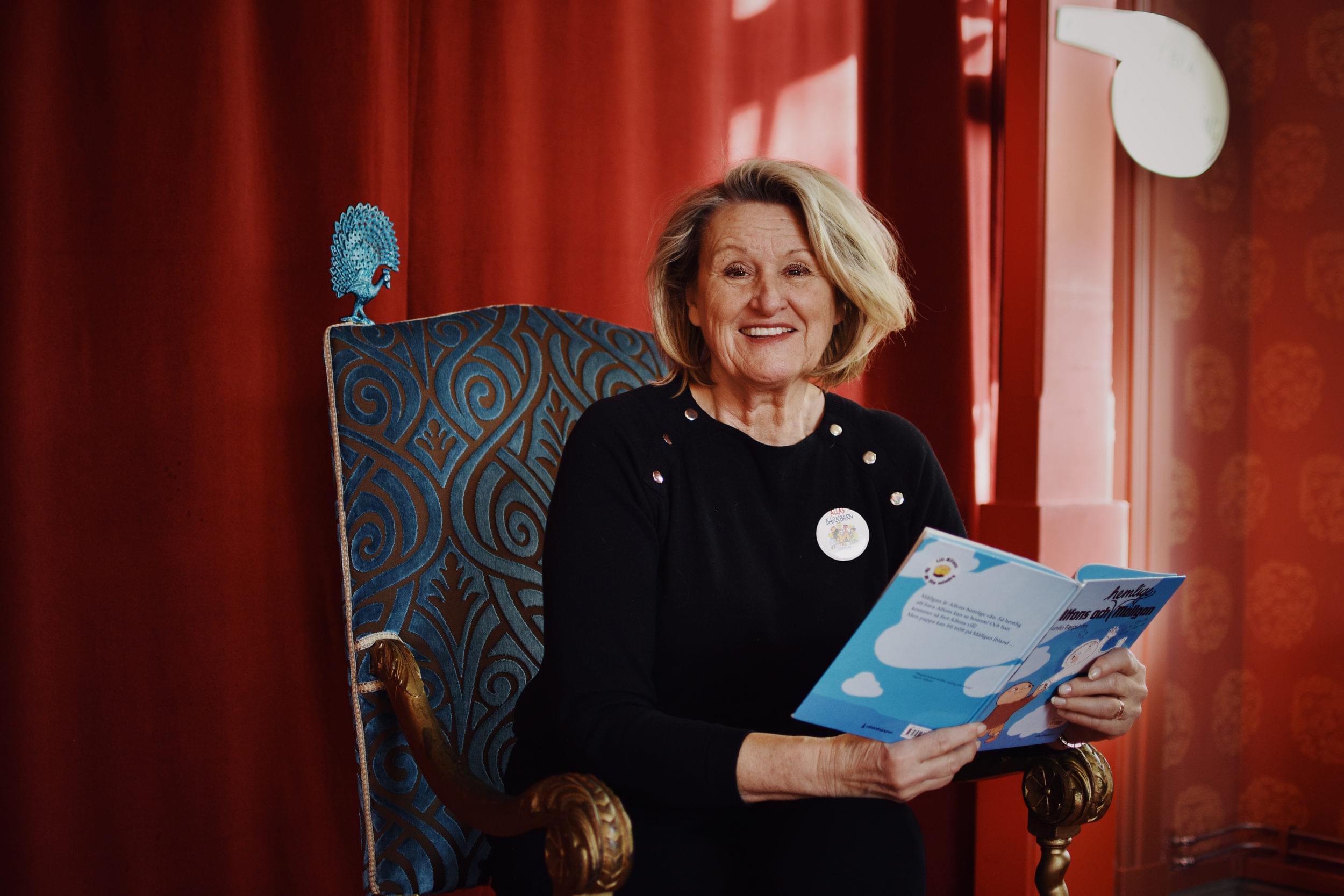 En leende sagotant i svart tröja sitter i en blå kungastol och läser ur en bok om Alfons Åberg. En glad sagotant sitter i en blå kungastol och läser ur en bok om Alfons Åberg.