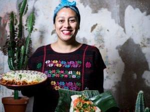 Kvinna i färgglada kläder står hållandes två tallrikar mat mot grå betongvägg