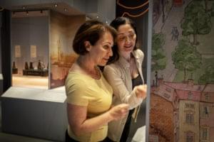 En äldre kvinna i gul tröja och en yngre kvinna pekar och tittar in i en monter i en utställning.
