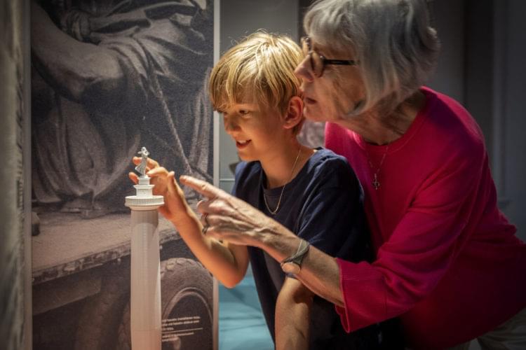 Ett barn känner på en interaktiv modell av Sjömanshustrun tillsammans med en äldre kvinna.