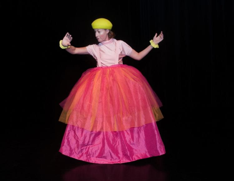 Kvinna i stor kjol, basker och teatersmink.