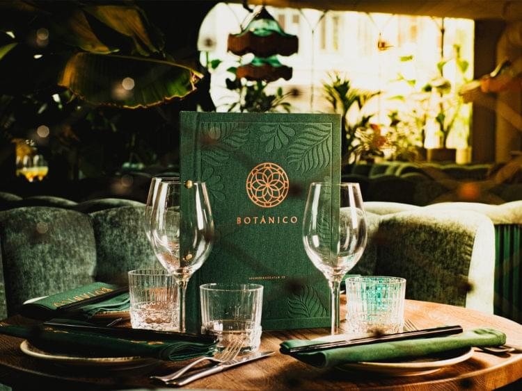 Två glas och en meny står på ett bord på restaurang Botanico