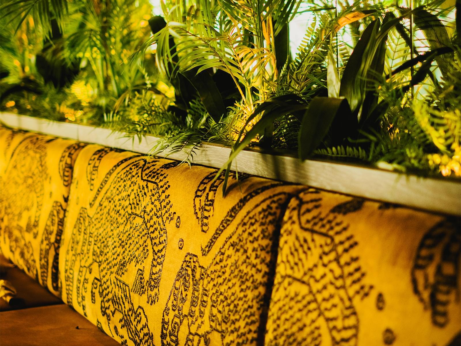 En gul soffrygg står framför ett hav av gröna djungelliknande växter