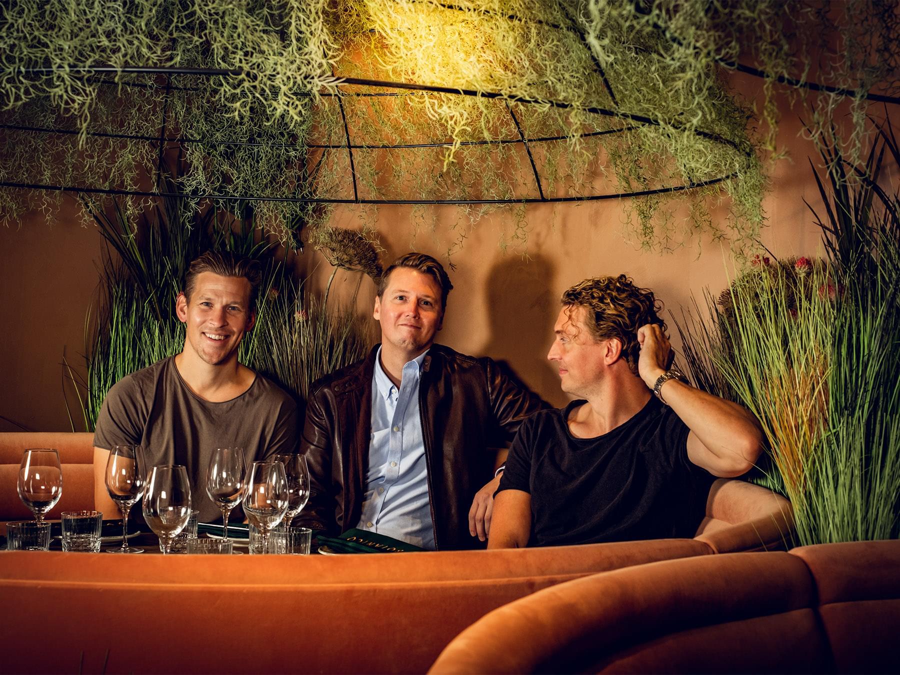 Tre män sitter på rad i en soffa