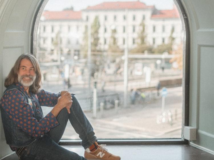 Man sitter i ett fönster som blickar ut över Järntorget.
